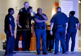 A Dallas police officer covers his face as he stands with others outside the emergency room at Baylor University Medical Center, Friday, July 8, 2016, in Dallas. Snipers opened fire on police officers in the heart of Dallas on Thursday night, killing some of the officers. (AP Photo/Tony Gutierrez)